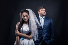 Tear-stained bride and brutal groom in suit. Disheveled bride with tear-stained face and brutal groom in suit, studio photo shoot, black background stock image