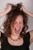 Tear your hair out. Young woman pulls hair and screams in frustration stock images