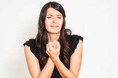 Tearful distressed woman wringing her hands and holding a ring Stock Photos
