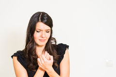 Tearful distressed woman wringing her hands and holding a ring Stock Image