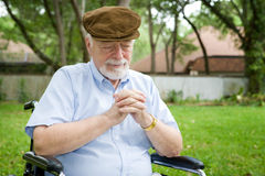 Tearful Prayer. Senior man in a wheelchair making a tearful prayer to God Royalty Free Stock Photos