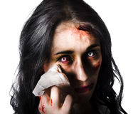 Zombie woman crying. Tearful zombie woman crying and wiping her face on tissue Royalty Free Stock Photos