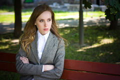 Tearful woman sits on the bench Stock Photo