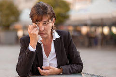Tearful woman sitting outdoors crying Royalty Free Stock Photos