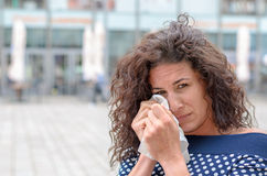 Tearful young woman wiping her eyes Royalty Free Stock Photo