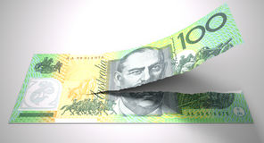 Tearing Australian Dollar Note. A concept picture of a regular australian one hundred dollar note tearing in two length ways on an isolated background Stock Image