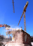 Tearing Down the House. Ongoing demolition of a brick house using an excavator, construction cranes in the background raising the new building on the Stock Photos