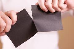 Tearing mens een stuk van document in halve lege zwarte vliegerbrochure Royalty-vrije Stock Foto's
