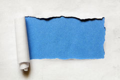 Tearing a paper frame hole with blue background Royalty Free Stock Images