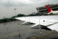 Tears of Goodbye. Raindrops on the window as the airplane prepares to leave Stock Photo
