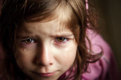 Teary Eyed Little Girl Trying Not to Laugh. A teary eyed little girl looks up at the camera with tears in her eyes. At firt look she looks upset, sad, or Royalty Free Stock Image