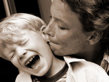Teaser. Mother biting into son's ear - aua-aua-aua Stock Photography