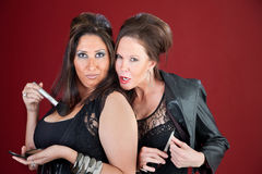 Teasing. Two cougers dressed in black tease each other and prepare their makeup Stock Photography