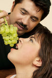 Teasing. Playfully offers or teases her with grapes Stock Image