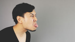 Teasing with his tongue. An asian guy with black t-shirt royalty free stock images