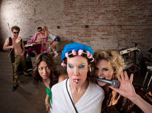 Teasing Neighbors at a Party. Young lady teasing a woman in curlers with a microphone at a 1970s Disco Music Party Royalty Free Stock Image