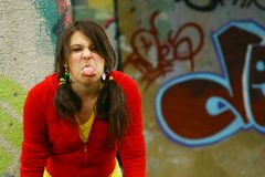 Teasing Teen. A teen girl standing against a graffiti wall teasing with her tongue stock photos