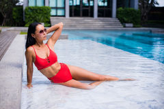 Teasing young smiling woman brunette beauty with red bikini rests laying on wet poolside marble enjoying summer in the. Outdoor swimming pool. Lifestyle, travel Stock Photo