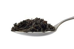 Teaspoom con la hoja de té del negro oscuro aislada Fotografía de archivo libre de regalías