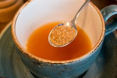 Teaspoon of brown cane sugar and a Cup of tea Royalty Free Stock Photo