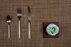 Teaspoon, fork, knife and a blue cupcake with cream. Breakfast sweet tooth. Royalty Free Stock Image