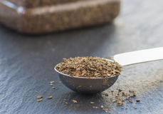 A teaspoon full of dried basil leaf Royalty Free Stock Images