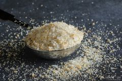 A teaspoon of garlic salt. Spilling onto a grey blue surface Royalty Free Stock Images