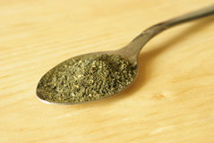 Teaspoon of Green Tea. A teaspoon full of green tea over a wooden background Stock Images