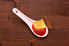 Teaspoon with hot sauce on wood from above Stock Image