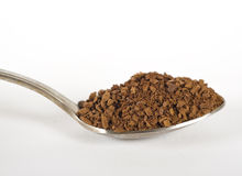 Teaspoon of instant coffee. Teaspoon containing a heap of instant coffee granules Royalty Free Stock Photos