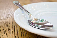 Teaspoon. A metal teaspoon on a saucer with a pattern reflected Royalty Free Stock Photography