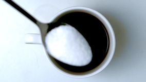 Teaspoon pouring sugar into cup of coffee. In slow motion stock footage