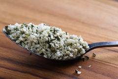 Teaspoon with raw shelled hemp seeds. Close up of a teaspoon filled with raw shelled help seeds on a wooden table Royalty Free Stock Image