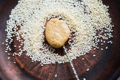 Teaspoon tahini paste, sesame seeds in a brown plate, top view Stock Image