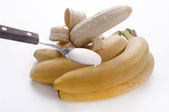 Teaspoon of yogurt to the banana Stock Image