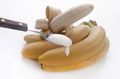Teaspoon of yogurt to the banana Stock Photo