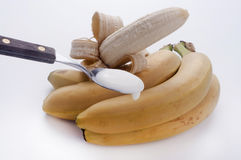 Teaspoon of yogurt to the banana. On a white background Stock Photos