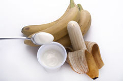 Teaspoon of yogurt to the banana Royalty Free Stock Image