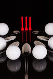 Teaspoons and golf equipments on the black glass table Royalty Free Stock Image