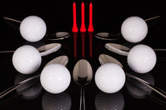 Teaspoons and golf equipments on the black glass table Royalty Free Stock Photography