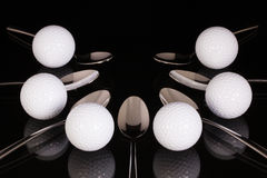 Teaspoons and golf equipments on the black glass table Royalty Free Stock Images