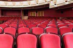 Teaterkorridor för besökare med härliga stolar av Bourgogne-röda sammetstolar för showen royaltyfri bild