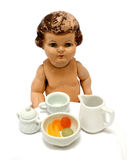 Teatime. Old antique doll with child's tea set Royalty Free Stock Images