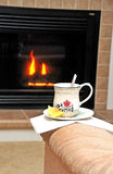 Teatime. Cup of tea on a recliners armrest in font of a fireplace Stock Image