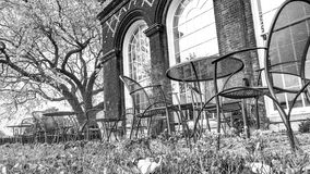 Teatime in Autumn. Black and white: Chairs and table in an english garden with orangery in the background. It's teatime stock photography