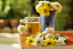 Teatime with Chinese pastry and tea and flower on a orange chair. Afternoon teatime with Chinese pastry and tea and flower on a orange chair in garden royalty free stock photo