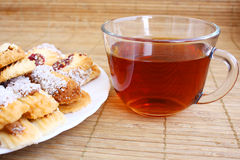 Teatime: close-up cup of tea and cookies on plate Royalty Free Stock Photos