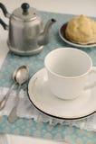 Teatime med eclairen snör åt på servetten Royaltyfria Bilder