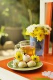 Teatime mit chinesischem Gebäck und Tee und Blume auf einem orange Stuhl Stockfotos