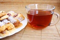 Teatime: Nahaufnahmetasse tee und Plätzchen auf Platte Lizenzfreie Stockfotos
